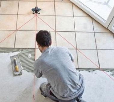 парень кладет плитку на полу