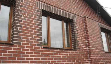 стена дома с окном отделана кирпичной кладкой