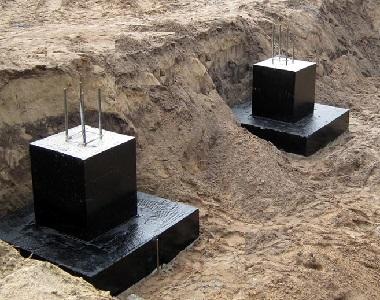Черные фундамент-стаканы с арматурой покрыты смолой