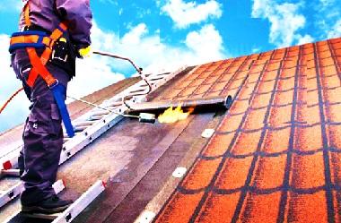 Рабочий паяльной лампой прогревает поверхность крыши