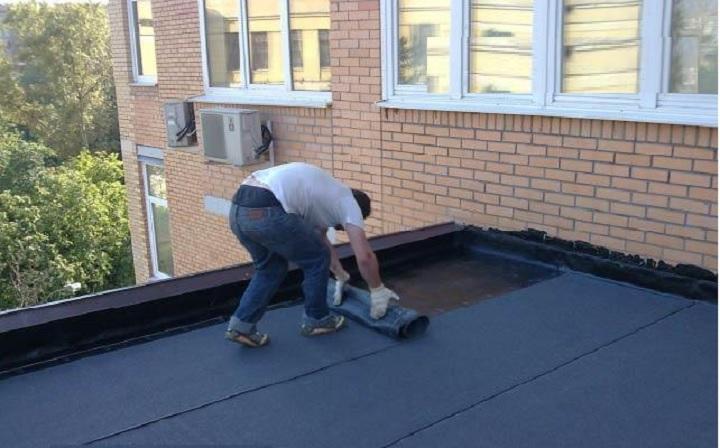 Раскатка рубероида на крыше