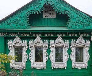 Зеленый дом с белыми наличниками